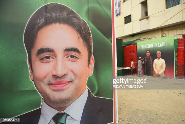 A supporter of Bilawal Bhutto Zardari Chairman of the Pakistan Peoples Party attaches an election poster on a wall in Karachi on July 2 2018 Pakistan...