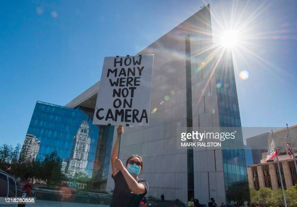 A supporter of Black Lives Matter holds a protest sign outside the Los Angeles Police Department headquarters as she demonstrates against the death...