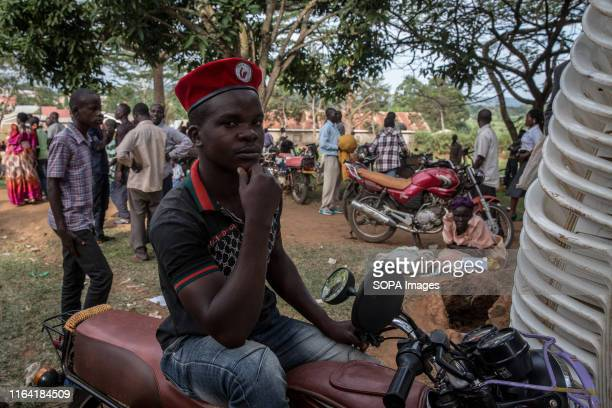 A supporter of Bobi Wine poses wearing the red beret associated with the people power during a campaign event in Gombe Bobi Wine whose real name is...
