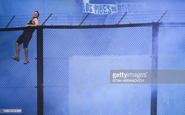 A supporter of Boca Juniors cheers during the first leg match of the allArgentine Copa Libertadores final against River Plate at La Bombonera stadium...