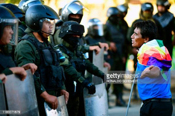 Supporter of Bolivian ex-President Evo Morales faces riot police during a demonstration in Cochabamba, on November 18, 2019. - Bolivia's influential...