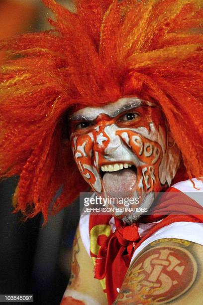 A supporter of Brazilian football team Internacional cheers before the start of the Libertadores Cup final match against Mexico's Chivas on August 18...