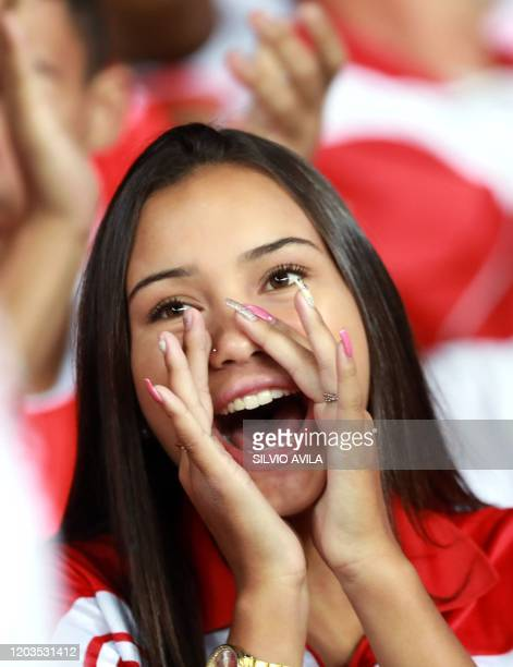 A supporter of Brazilian Internacional cheers for her team during a Libertadores Cup football match against Colombia's Deportivo Tolima at BeiraRio...