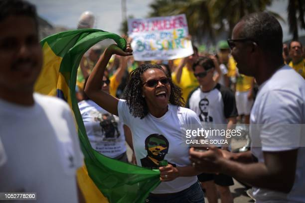 A supporter of Brazil's presidential rightfar candidate Jair Bolsonaro takes part in a rally in Copacabana Rio de Janeiro on October 21 2018...