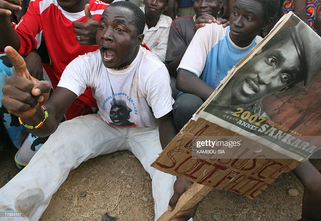 A supporter of Captain Thomas Sankara holds a placard with Sankara's picture reading 'Justice will be made' 15 October 2007 in Ougadougou, as Sankara's widow, Mariam arrives to lay a wreath at her husband's grave on the 20th annniversary of his death. Mariam arrived 14 October 2007 on her first trip home since her husband assassination to take part in a commemoration of her husband alongside the anniversary celebrations to marked the 20th anniversary in power of President Blaise Compaore. Burkina Faso is set to be divided as it marks two paradoxical events: some will pay homage to a fallen hero and ex-leader Thomas Sankara while others celebrate the re-birth of democracy under his successor. The charismatic captain Sankara and father of the west African nation's revolution was killed on October 15, 1987 in a coup which brought his former friend and comrade-in-arms, Blaise Compaore, to power.
