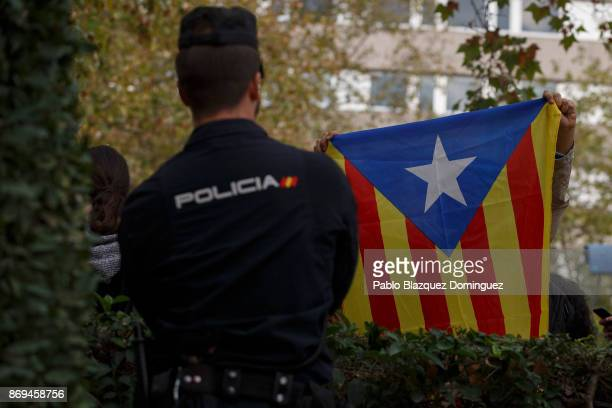 A supporter of ceased members of the Catalan government displays proindependence Catalan flag after learning they will be sent to jail outside...