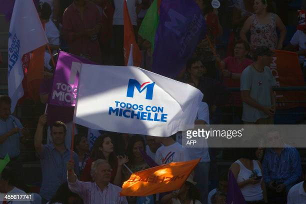 A supporter of Chilean presidential candidate for the New Majority coalition Michelle Bachelet holds a flag with her name during her electoral...
