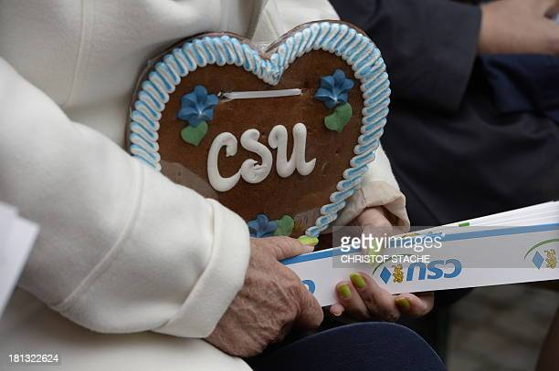 A supporter of Christian social Union wears a traditional gingerbread heart reading CSU while waiting before a campaign event of the Christian...