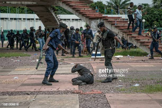 Supporter of Congolese presidential candidate Martin Fayulu protect himself as policemen close on him outside the Constitutional Court in Kinshasa on...