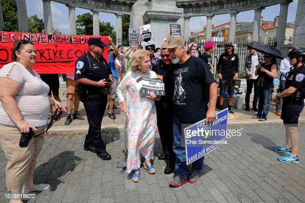 A supporter of conserving Confederate monuments Helen Marie Taylor is ushered away from counter protesters as they rally at the Jefferson Davis...