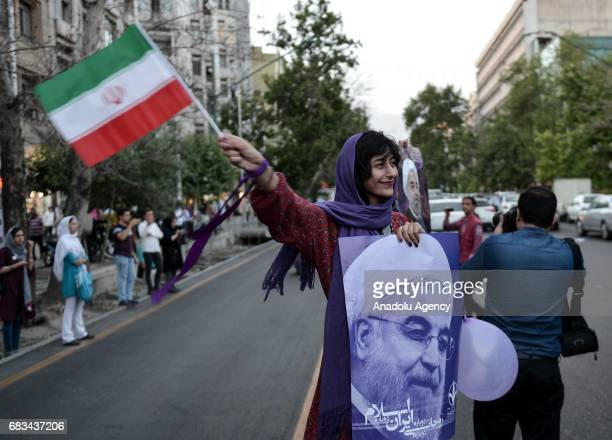 A supporter of current President of Iran Hassan Rouhani holds a banner of Rouhani as she waves an Iranian flag ahead of the Iranian presidential...