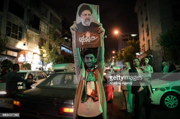 A supporter of current President of Iran Hassan Rouhani holds a banner of Rouhani ahead of the Iranian presidential election in the streets of Tehran...