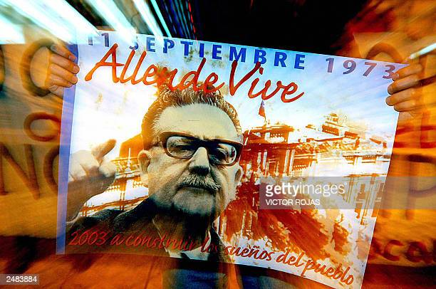 A supporter of deceased socialist President Salvador Allende holds a banner with Allende's photograph during a commemorative demonstration and...
