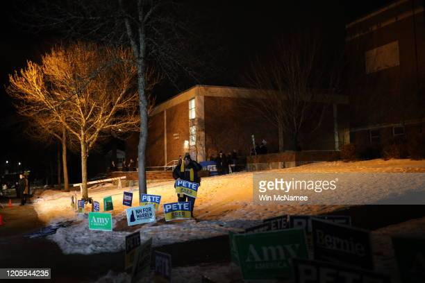 Supporter of Democratic presidential candidate former South Bend, Indiana Mayor Pete Buttigieg places campaign signs before the opening of a polling...