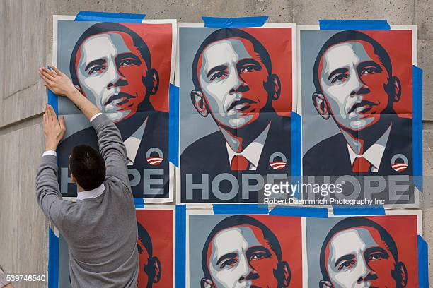 A supporter of Democratic presidential hopeful Barack Obama pastes up posters outside the Rec Sports Center at the Univeristy of Texas at Austin...