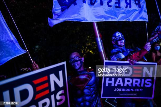 Supporter of Democratic presidential nominee and former Vice President Joe Biden dressed as Super Man shouts slogans as he waits for Biden's arrival...