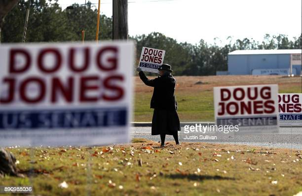 A supporter of democratic Senatorial candidate Doug Jones holds a sign outside of a polling station at the Bessemer Civic Center on December 12 2017...