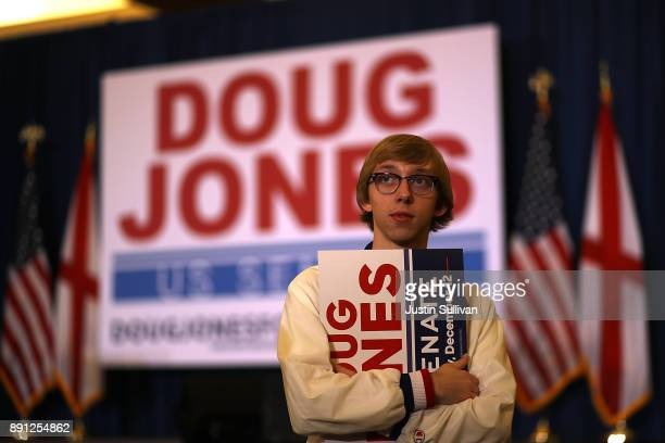 A supporter of democratic US Senatorial candidate Doug Jones holds a sign as he watches election returns during an election night gathering the...