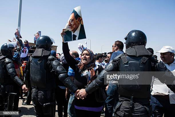 A supporter of deposed Egyptian President Hosni Mubarak holds a poster of the former dictator at the start of the retrial of Mubarak at the Cairo...