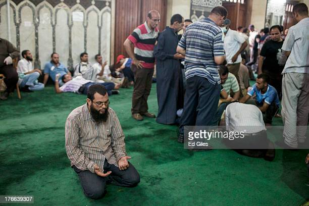 A supporter of deposed Egyptian President Mohammed Morsi prays on the floor of the Fateh Mosque at Ramses Square as an injured protesters is treated...