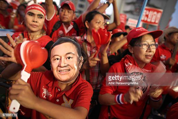 A supporter of deposed Thai Prime Minister Thaksin Shinawatra wearing a mask of Thaksin Shinawatra shouts slogan during a protest on March 14 2010 in...