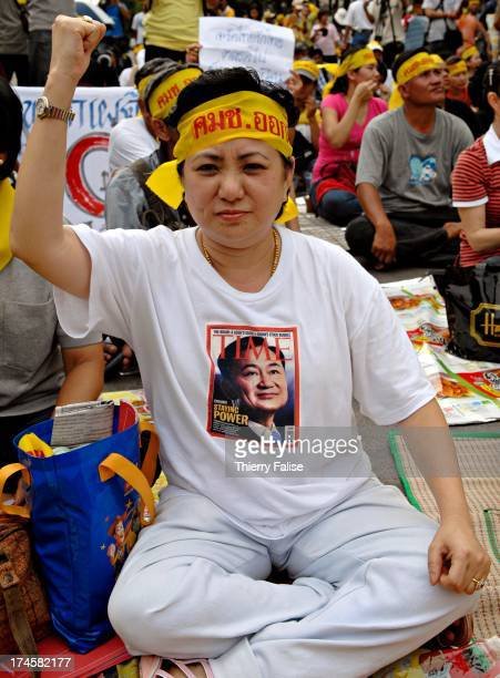 Supporter of deposed Thai Prime Minister Thaksin Shinawatra wears a t-shirt with a reproduction of Thaksin's picture on a Time magazine cover. A few...