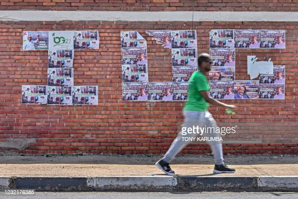 Supporter of Djibouti President Ismail Omar Guelleh walks past campaign posters pasted against a wall to spell out the leaders initials 'I.O.G.' in...