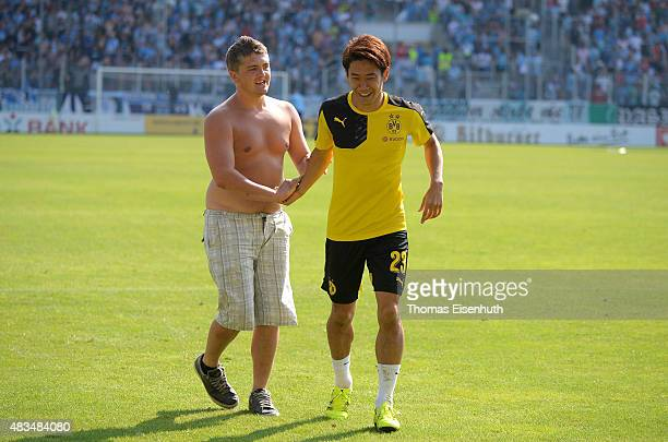 A supporter of Dortmund runs on the pitch and talks with Shinji Kagawa after the DFB Cup first round match between Chemnitzer FC and Borussia...