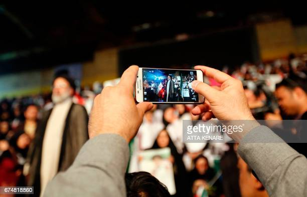 A supporter of Ebrahim Raisi takes a picture of the Iranian presidential candidate during a campaign rally in the capital Tehran on April 29 2017 /...