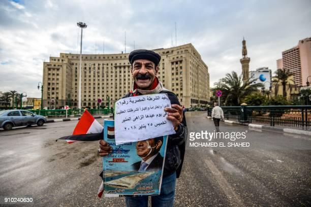 A supporter of Egyptian President Abdel Fattah alSisi stands in Tahrir square with his portrait and a sign on a piece of paper reading in Arabic The...