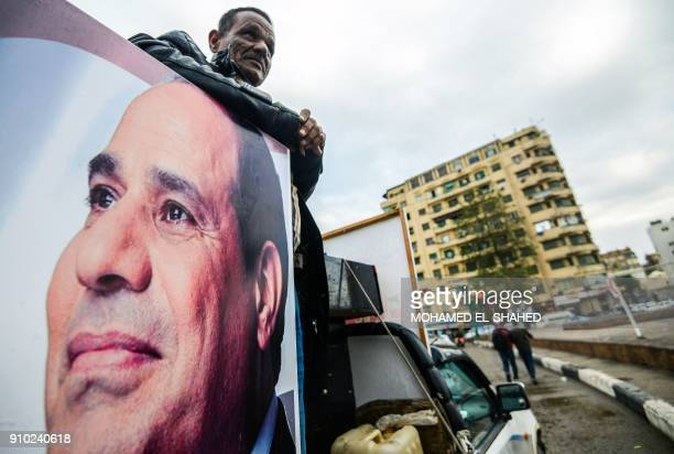 A supporter of Egyptian President Abdel Fattah alSisi stands in the back of a pickup truck bearing his portrait and loudspeakers in the capital...