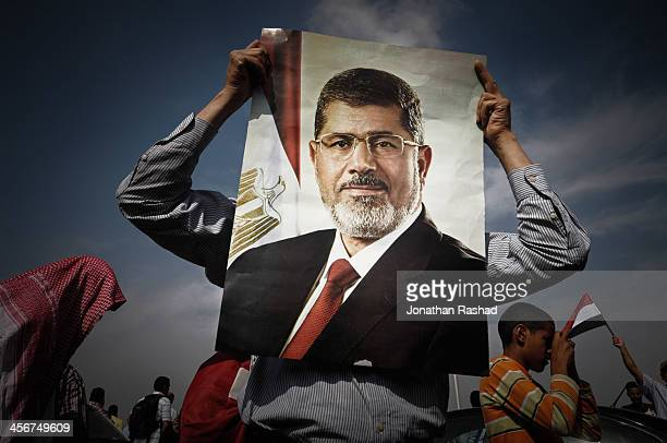 A supporter of Egypt's deposed president Mohamed Morsi holds a portrait of Morsi during a protest outside Police Academy in Cairo 4 November 2013 On...