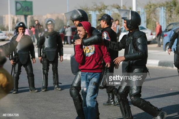 A supporter of Egypt's Muslim Brotherhood is arrested by Egyptian riot police after taking part in a small protest prior to the planned trial of...