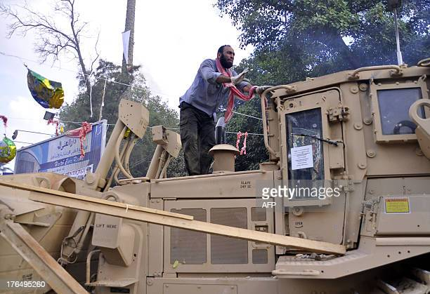 Supporter of Egypt's ousted president Mohamed Morsi climbs on a bulldozer as security forces moved in to disperse protesters from a huge camp in...