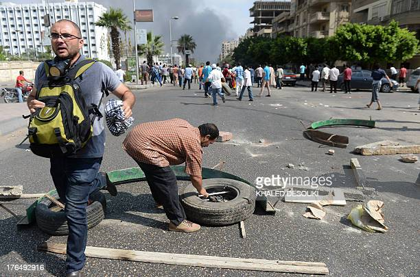 Supporter of Egypt's ousted president Mohamed Morsi tries to build a barricade as others run for cover during clashes with riot police as they try to...