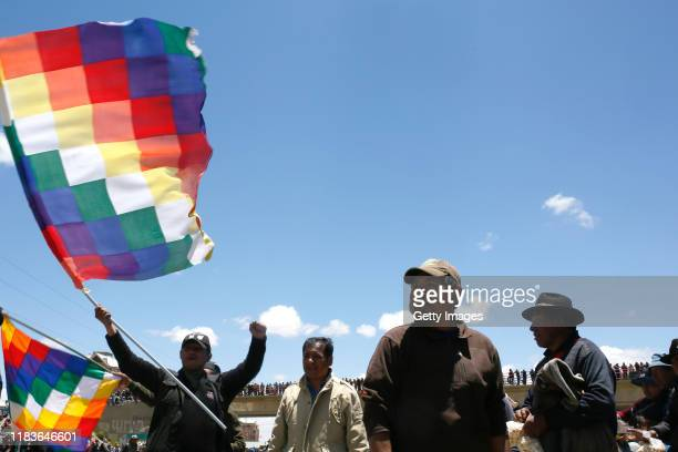 A supporter of Evo Morales holds a Whipala flag and shouts slogans against Interim President Jeanine Añez during a blockade to the road to the...