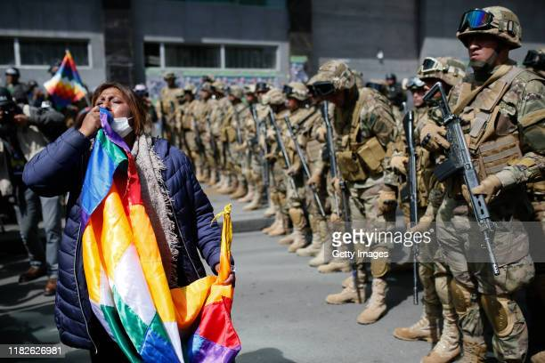 A supporter of Evo Morales holds a Whipala flag in front of the military police during a protest on November 15 2019 in La Paz Bolivia Morales flew...