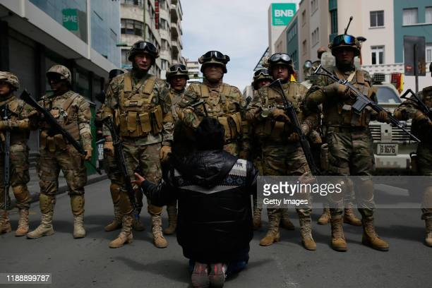 A supporter of Evo Morales kneels and gestures with his arms open in front of the military police officers on November 15 2019 in La Paz Bolivia...