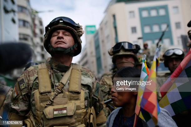 A supporter of Evo Morales member of an indigenous community holds Whipala flags in front of the military police during a protest on November 15 2019...