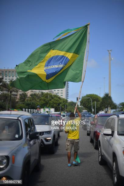 A supporter of farright lawmaker and presidential candidate for the Social Liberal Party Jair Bolsonaro waves a Brazilian flag in Rio de Janeiro...
