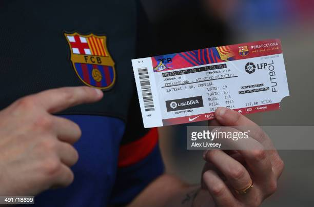 A supporter of FC Barcelona shows off his match ticket prior to the La Liga match between FC Barcelona and Club Atletico de Madrid at Camp Nou on May...