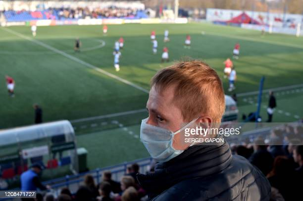 TOPSHOT A supporter of FC Minsk wears a facemask for protective measures amid concerns over the spread of the COVID19 as he attends the Belarus...