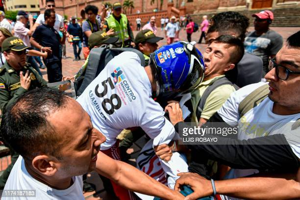 A supporter of former Colombian President Alvaro Uribe wearing a helmet hits an opponent holding a banner against him during a rally in his support...