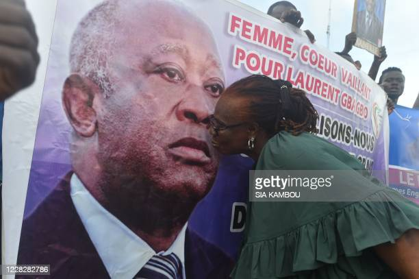 TOPSHOT A supporter of former Ivorian President Laurent Gbagbo president of the Ivorian Popular Front gesture next to a banner in Abidjan on August...
