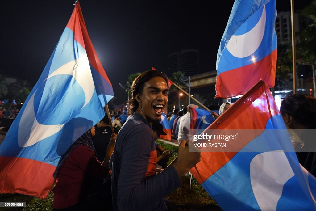 A supporter of former Malaysian prime minister and opposition candidate Mahathir Mohamad celebrate in Kuala Lumpur on early May 10, 2018. - Malaysia's opposition alliance headed by veteran ex-leader Mahathir Mohamad, 92, has won a historic election victory, official results showed on May 10, ending the six-decade rule of the Barisan Nasional (BN) coalition.