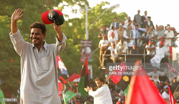 A supporter of Former Pakistani Prime Minister Benazir Bhutto waves in front of her convoy from Karachi international airport 18 October 2007 Bhutto...