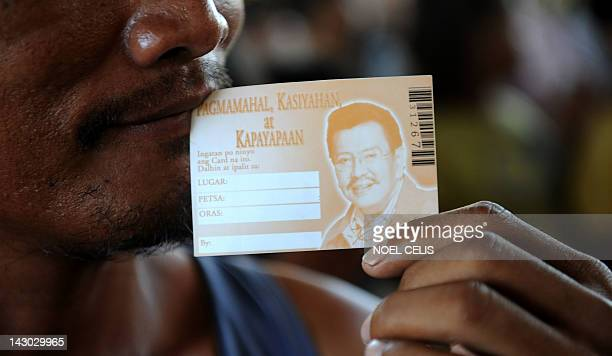 A supporter of former Philippine president Joseph Estrada holds a gift coupon as he queues up to receive gifts distributed by Estrada at a slum area...