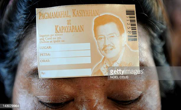 A supporter of former Philippine president Joseph Estrada is seen with coupon stuck on her forehead as he queues up to receive gifts distributed by...