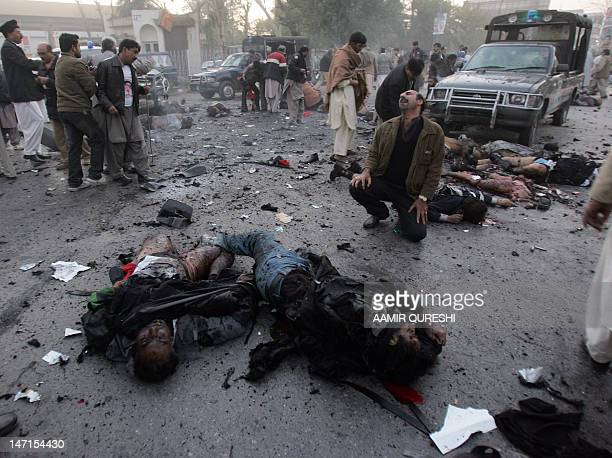 A supporter of former premier Benazir Bhutto cries as he sits among bodies after the bomb blast in Rawalpindi 27 December 2007 Benazir Bhutto died in...