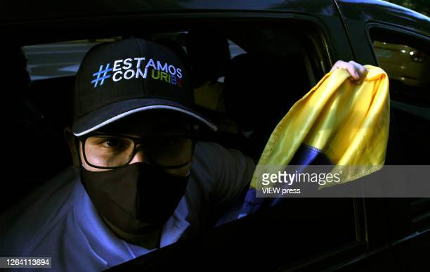 A supporter of former President and Senator Alvaro Uribe Velez wearing a protective mask poses with a hat that reads in spanish we stand with Uribe...